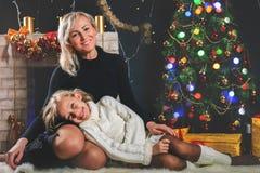 La mère et la fille heureuses près ont décoré l'arbre de Noël Image stock