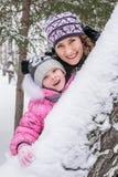 La mère et la fille marchent dans les bois d'hiver Photo stock