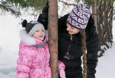 La mère et la fille marchent dans les bois d'hiver Photographie stock libre de droits