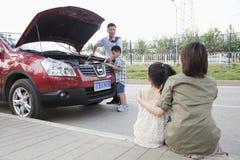 La mère et la fille observent comme essai de père et de fils pour fixer la voiture Images stock