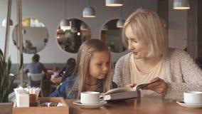 La mère et la fille ont lu le livre au café banque de vidéos