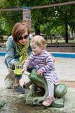 La mère et la fille ont pulvérisé l'eau en parc Images libres de droits