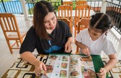 La mère et la fille passent commande du menu Image libre de droits