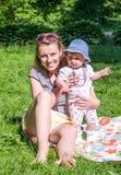 La mère et la fille s'asseyent sur l'herbe en parc Photos libres de droits