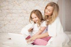 La mère et la fille s'asseyent sur le lit dans des pyjamas et ont l'amusement, utilisent l'ordinateur portable lifestyle Famille  image stock