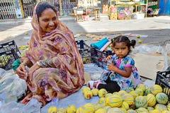 La mère et la fille s'asseyent sur le trottoir près des melons Photo stock