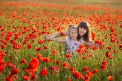 La mère et la fille souriant dans un pavot mettent en place Le pique-nique dans le domaine de pavot Promenade avec la famille dan Photographie stock libre de droits