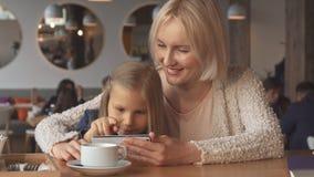 La mère et la fille utilisent le smartphone au café banque de vidéos