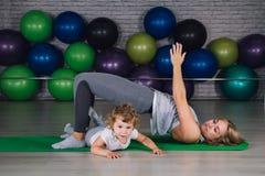 La mère et le bébé font des exercices ensemble dans le gymnase photo stock