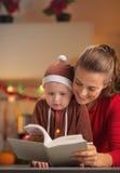 La mère et le bébé heureux dans Noël costument le livre de lecture Photographie stock libre de droits