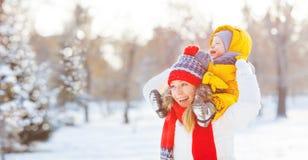 La mère et le bébé heureux de famille est neige heureuse sur la promenade d'hiver Photographie stock libre de droits