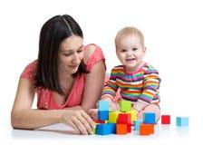 La mère et le bébé jouent avec les blocs constitutifs jouent d'isolement sur le blanc Image libre de droits