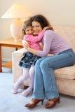 La mère et le descendant de sourire s'asseyent sur le divan Photographie stock