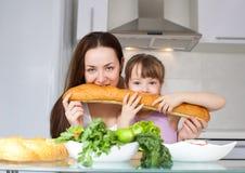 La mère et le descendant mangent du pain Images stock
