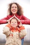 La mère et le fils affichent la maison des mains Photos stock