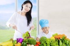 La mère et le fils attirants font la salade Photos stock