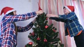 La mère et le fils dans des chapeaux de Noël ont placé la flèche sur l'arbre de Noël banque de vidéos