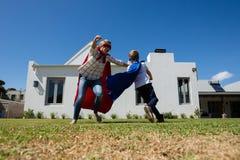 La mère et le fils dans le super héros costument jouer dans l'arrière-cour Images libres de droits