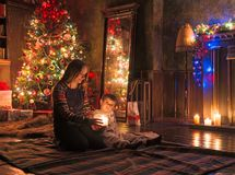 La mère et le fils dans Noël mystérieusement allumé ont décoré la pièce images libres de droits