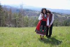 La mère et le fils de sourire se sont habillés dans des costumes bulgares de folklore Photos stock