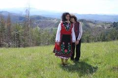 La mère et le fils de sourire se sont habillés dans des costumes bulgares de folklore Photos libres de droits