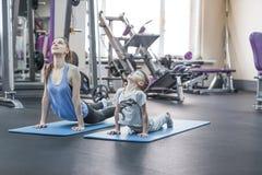 La mère et le fils faisant le yoga s'exercent au gymnase Photo stock