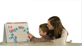 La mère et le fils font la maman de mot sur le bureau sur le fond blanc d'isolement Photos stock