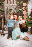 La mère et le fils heureux s'asseyent dans des décorations de Noël prenant le selfie Photographie stock libre de droits