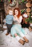 La mère et le fils heureux s'asseyent dans des décorations de Noël prenant le selfie Photos libres de droits