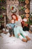 La mère et le fils heureux s'asseyent dans des décorations de Noël prenant le selfie Image libre de droits