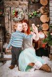 La mère et le fils heureux s'asseyent dans des décorations de Noël prenant le selfie Images libres de droits