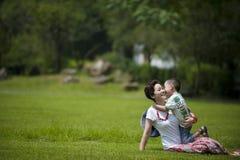 La mère et le fils jouent dans l'herbe Photographie stock