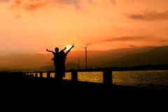 la mère et le fils montrent la liberté de main au Ba de coucher du soleil de rivière Images stock