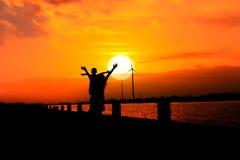 la mère et le fils montrent la liberté de main au Ba de coucher du soleil de rivière Photo stock