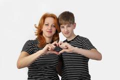 La mère et le fils montrent le coeur par des doigts sur le gris Images libres de droits