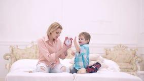 La mère et le fils ont installé un réveil dans la chambre à coucher sur le lit Concept de temps de sommeil Une famille heureuse banque de vidéos
