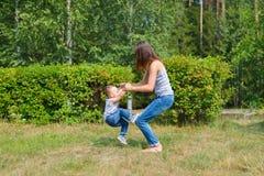 La mère et le fils ont l'amusement jouant dans le parc Enfant de Littkek faisant à étapes les mamans finies ascendantes jambes Photo stock