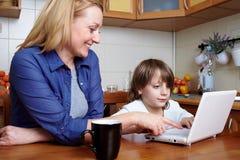 La mère et le fils s'assied dans la cuisine et l'ordinateur portatif d'utilisation Image stock