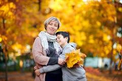 La mère et le fils sont en parc de ville d'automne Ils sont des parents posant, souriant, jouant et ayant l'amusement Arbres jaun photos stock