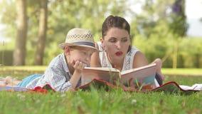 La mère et le fils sont rédigés en lisant un livre en parc d'été banque de vidéos