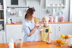 La mère et le fils sourient tout en prenant un petit déjeuner dans la cuisine Photo libre de droits