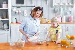 La mère et le fils sourient tout en prenant un petit déjeuner dans la cuisine La maman verse des flocons de lait et d'avoine dans Photo stock