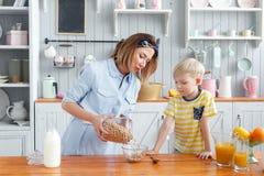 La mère et le fils sourient tout en prenant un petit déjeuner dans la cuisine La maman verse des flocons de lait et d'avoine dans Images libres de droits