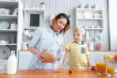 La mère et le fils sourient tout en prenant un petit déjeuner dans la cuisine La maman verse des flocons de lait et d'avoine dans Image stock
