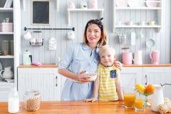 La mère et le fils sourient tout en prenant un petit déjeuner dans la cuisine Regardez l'appareil-photo Photos stock