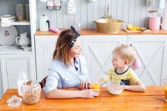 La mère et le fils sourient tout en prenant un petit déjeuner dans la cuisine Regardez l'un l'autre Images libres de droits