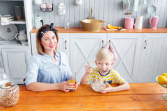 La mère et le fils sourient tout en prenant un petit déjeuner dans la cuisine Images stock