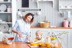 La mère et le fils sourient tout en prenant un petit déjeuner dans la cuisine La maman verse le lait dans le verre Photos libres de droits
