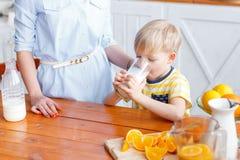 La mère et le fils sourient tout en prenant un petit déjeuner dans la cuisine La maman verse le lait dans le verre Image stock