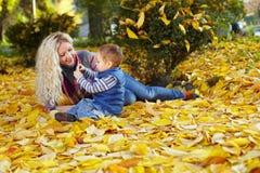 La mère et le fils sur les lames tombées en automne stationnent Photographie stock libre de droits